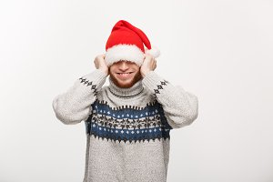 Holiday Concept - Young beard man in sweater enjoy playing with santa hat.