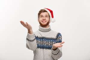 Christmas Concept - young cool beard man in sweater with waiting for snow gesture.