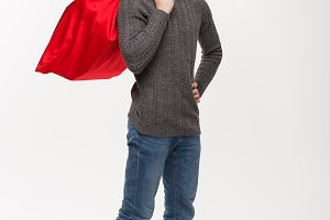 Christmas concept - Young confident smart man holding red big santa bag with a lot of present inside.