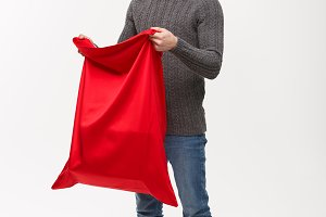 Christmas concept - Young beard handsome man exciting open santa big bag for present.