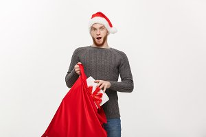 Christmas Concept - Young happy beard man excite with big present in santa bag.