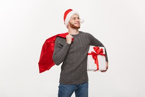 Christmas Concept - Young happy beard man holding santa bag and white present.