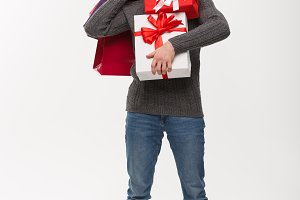 Christmas Concept - young handsome man with beard holding heavy presents and shopping bags with exhausted facial expression on white background.
