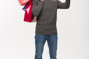 Christmas Concept - attractive young caucasian man surprising shocking holding shopping bag and pointing finger in front.