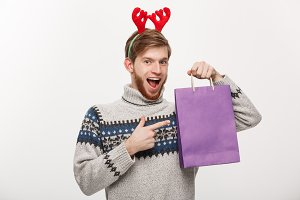 Christmas Concept - Young handsome beard man happy with shopping bag in the hand isolated on white.