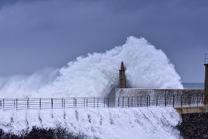 Stormy wave over lighthouse.