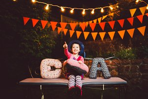 a funny child the girl sits on a bench in a festive decorated yard decor with bright garlands of lanterns. She learns the alphabet in a playful form. Holds letters in the form of soft pillows