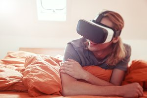 Young Man Lying On Bed With VR Glasses