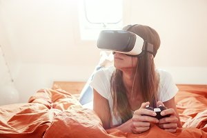 Young Woman Lying On Bed, Using Vr Glasses