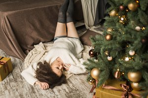 girl lies next to the christmas tree
