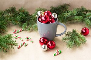 Silver and red christmas decorations balls in cup with fir tree christmas background