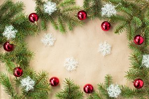 Festive christmas border with red balls on fir branches and snowflakes on rustic beige background