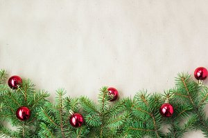 Fir tree branches decorated with red christmas balls as border on a rustic holiday background frame with copy space