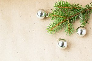 Fir tree branches decorated with silver christmas balls as border on a rustic holiday background frame with copy space