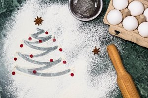 Christmas tree with the flour, berries and anise star spices as a decoration and rolling pin, eggs, strainer