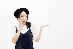 Young and pretty Asian woman in surprised and amazed expression presenting product gesture - with copy space