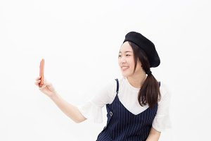 Young and pretty Asian woman in artist costume taking selfie with mobile phone in white isolated background