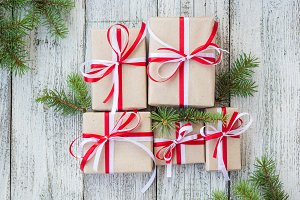 Christmas gift boxes with red and white ribbon on wooden background with Fir branches.