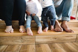 Beautiful young family. Bare feet of mother, father and children