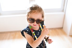 Cute little girl in dress and big sunglasses at home.