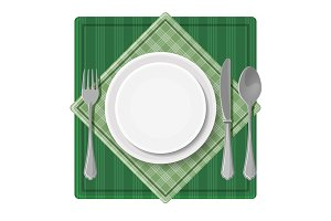 Served dinner plate with cutlery spoon fork and knife on green