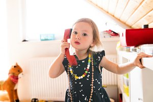 Cute little girl in dress wearing red lipstick making phone call