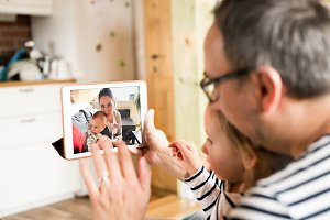 Young father videochatting with mother on tablet.