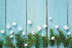 Christmas border with branch of fir tree and marshmallows on wooden background