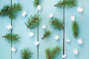 Christmas pattern with branch of fir tree and marshmallows on wooden background