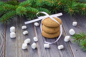 Christmas Gingerbread cookies with decorations and marshmallows on background with christmas tree
