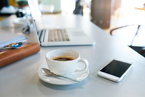 Office desk with coffee cup, smartphone and laptop.