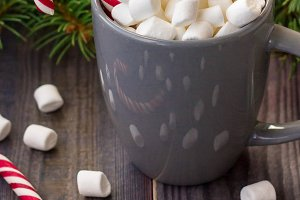Hot coffee chocolate with marshmallow on rustic wooden table background, candy canes gift boxes fir tree