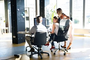 Three business people in the office talking together.