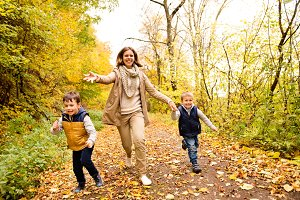 Beautiful mother with her sons in autumn forest.