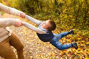 Unrecognizable father with son, spinning him. Autumn nature.