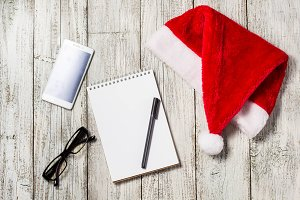 Christmas and New Year background with smartphone, red Santa hat, glasses, notepad and pen for your wishes
