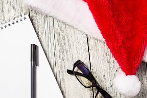 Christmas and New Year background with red Santa hat, glasses, notepad and pen for your wishes
