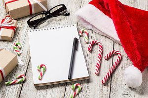 Christmas and New Year Items with Copy Space Santa Cap Notepad Pen Glasses and decorated Gift Boxes