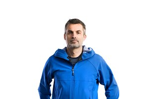 Mature hipster man in blue jacket. Studio shot, isolated.