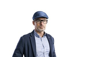 Mature hipster man in shirt, jacket and hat. Studio shot, isolat