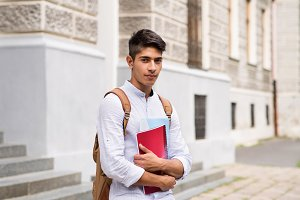 Handsome teenage student in front of old building.