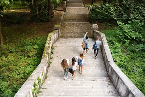 Teenage students walking on stone steps in front of university.