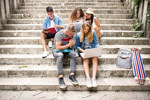 Teenage students with laptop outside on stone steps.