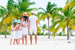 Young family on beach vacation in palm grove