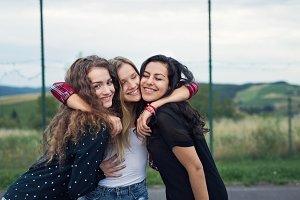 Three attractive teenage girls outdoors on playground.