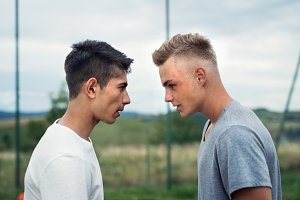 Two boys on playground looking at each other with hate.