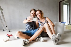 Couple at home painting walls, taking selfie with smartphone.