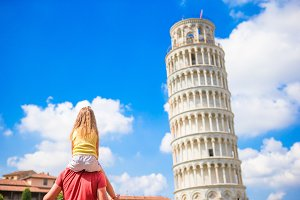 Family of father and little kid background the Learning Tower in Pisa. Pisa - travel to famous places in Europe.