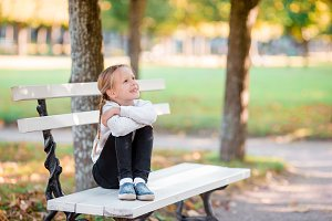 Cute kid sitting lost in thought at beautiful autumn day outdoors. Little girl on the bench in fall
