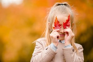 Adorable little girl outdoors at beautiful warm day in autumn park with yellow leaf in fall